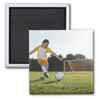 A young girl playing soccer on a soccer field in magnet