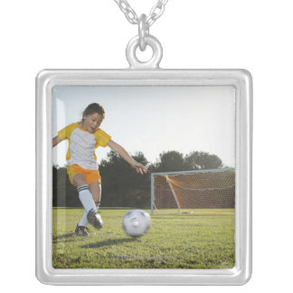 A young girl playing soccer on a soccer field in silver plated necklace