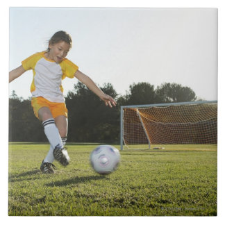A young girl playing soccer on a soccer field in tile