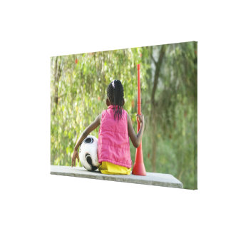 A young girl sits on a bench, holding a Vuvuzela Canvas Print