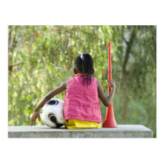 A young girl sits on a bench, holding a Vuvuzela Postcard