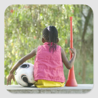 A young girl sits on a bench, holding a Vuvuzela Square Sticker