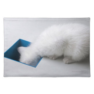 A Young Kitten Stretches His Head Down a Square Placemat