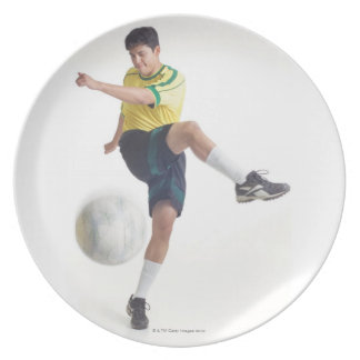 a young latin male wears a yellow soccer jersey party plates