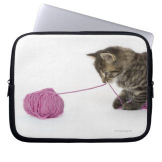 A young tabby kitten playing with a ball of laptop sleeve
