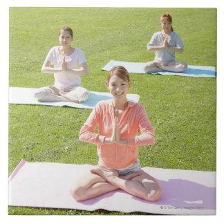 A young woman doing yoga tile