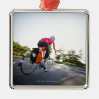 A young woman rides a bike around a park at Silver-Colored square decoration
