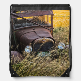 Abandoned old car in tall grass drawstring bag