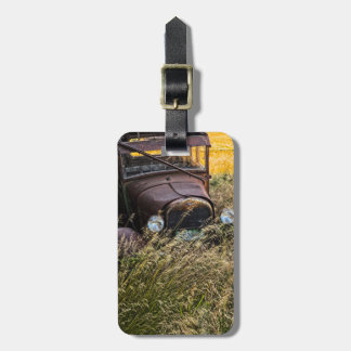 Abandoned old car in tall grass luggage tag