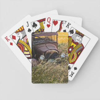 Abandoned old car in tall grass poker deck