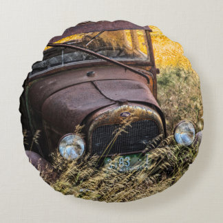 Abandoned old car in tall grass round cushion