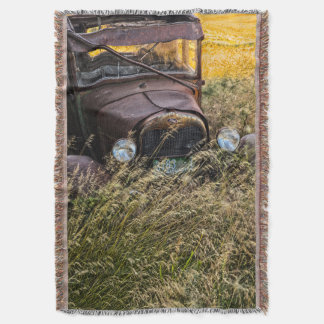 Abandoned old car in tall grass throw blanket