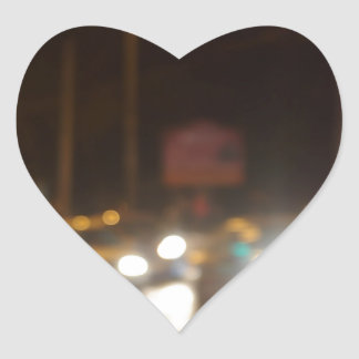 Abstract blurred image of a night scene with brigh heart sticker