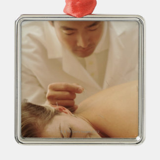 Acupuncturist putting needles in woman's back christmas ornament