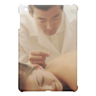 Acupuncturist putting needles in woman's back iPad mini case