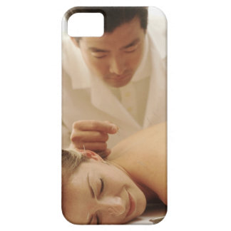 Acupuncturist putting needles in woman's back iPhone 5 cases