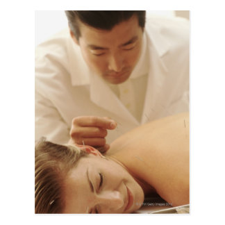 Acupuncturist putting needles in woman's back postcard
