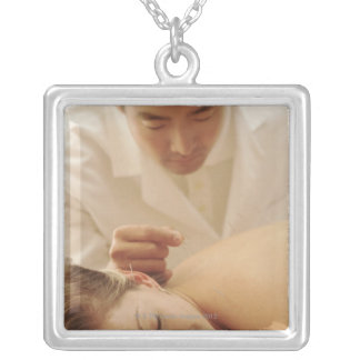 Acupuncturist putting needles in woman's back silver plated necklace