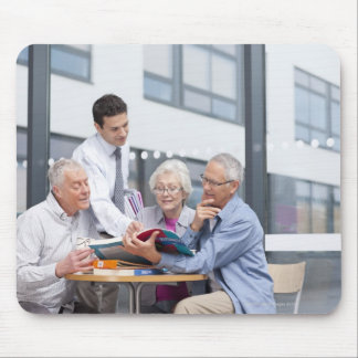 Adult students and teacher studying together in 2 mouse mat