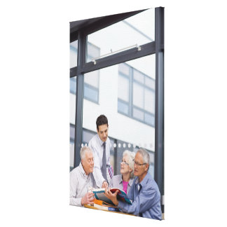 Adult students and teacher studying together in gallery wrap canvas