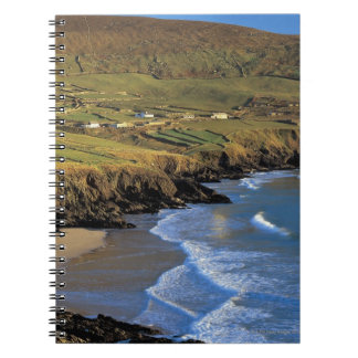 aerial view of waves washing up against a spiral notebook