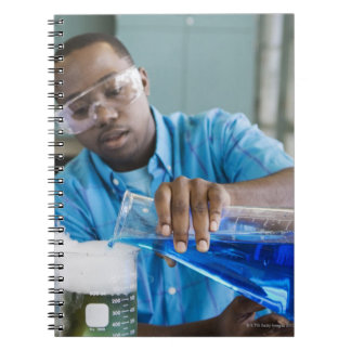 African man performing experiment in chemistry notebooks