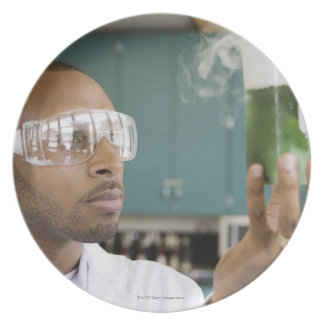 African scientist examining experiment in dinner plate