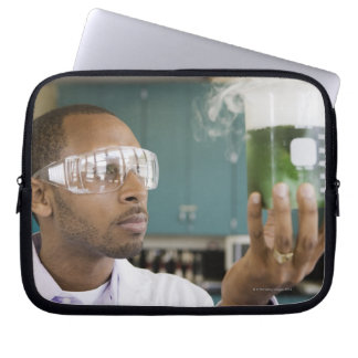 African scientist examining experiment in laptop computer sleeves