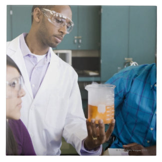 African teacher and students watching experiment tile