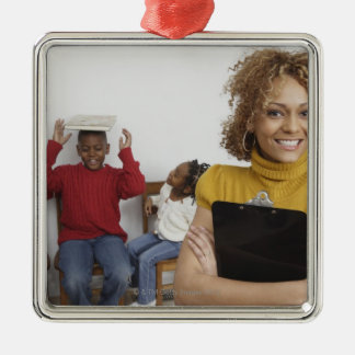 African teacher holding clipboard in front of christmas ornament