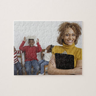 African teacher holding clipboard in front of puzzle