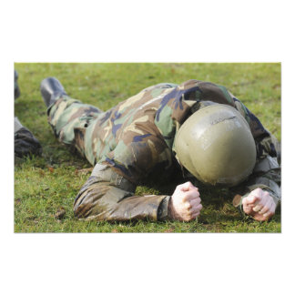 Airman crawls through a wet field photo