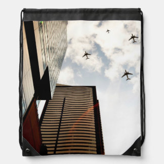 Airplanes flying over buildings drawstring bag