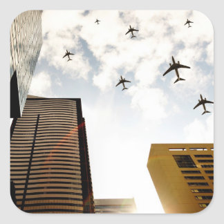 Airplanes flying over buildings square sticker