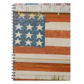 American flag painted onto fireworks stand near spiral notebook