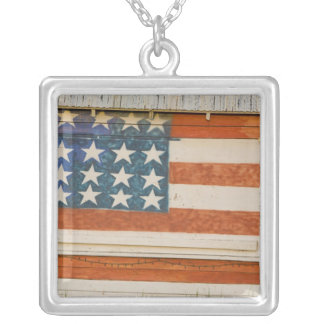American flag painted onto fireworks stand near square pendant necklace