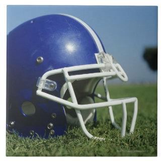American football helmet in grass,close-up tile