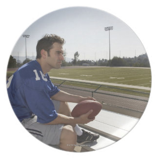 American football player sitting on bleachers party plates