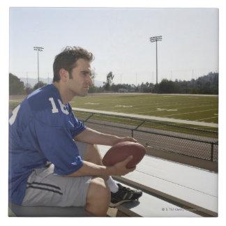 American football player sitting on bleachers tile