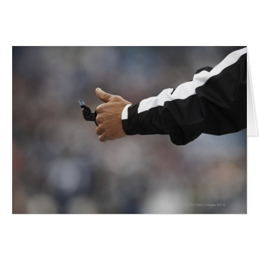 American football referee holding whistle, card