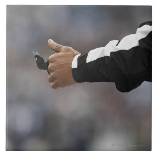 American football referee holding whistle, tile