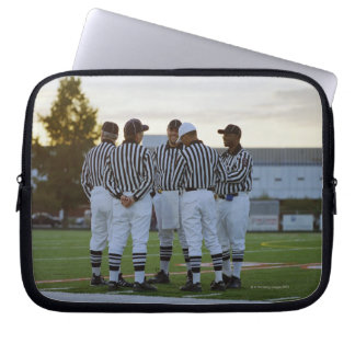 American football referees talking in field laptop computer sleeves