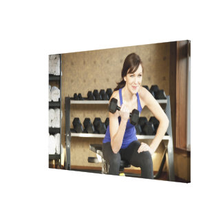 An active female lifting weights in a private canvas print