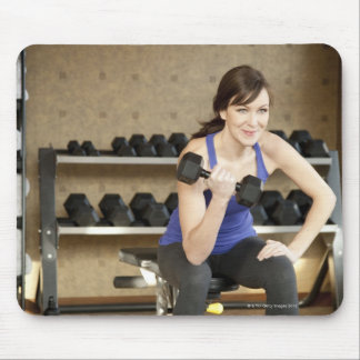 An active female lifting weights in a private mouse mat