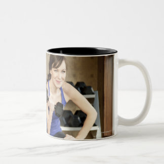 An active female lifting weights in a private Two-Tone mug
