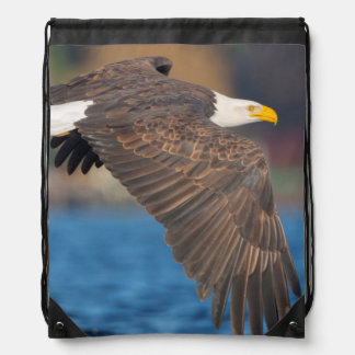 An adult Bald Eagle flies low over water Drawstring Bag