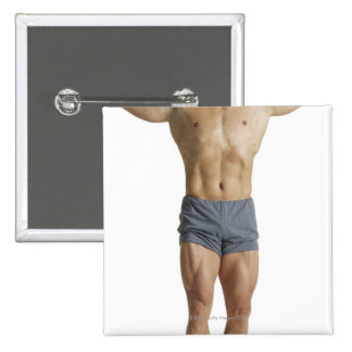 an adult caucasian male bodybuilder holds his 15 cm square badge