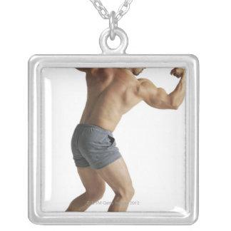 an adult caucasian male bodybuilder shows off square pendant necklace