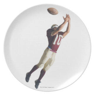 an african american football player in a red and plate