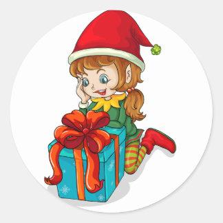 An elf beside a gift classic round sticker